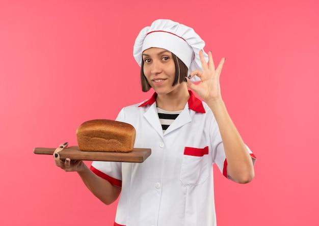 Glimlachende jonge vrouwelijke kok in eenvormige chef-kok die scherpe raad met brood erop houdt en ok teken doet dat op roze muur wordt geïsoleerd
