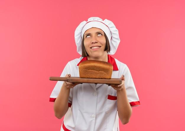 Glimlachende jonge vrouwelijke kok in eenvormige chef-kok die scherpe raad met brood erop houdt en omhoog geïsoleerd op roze muur kijkt