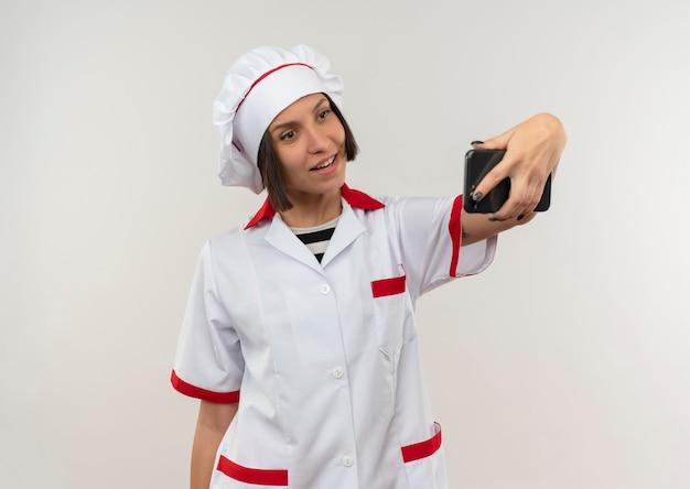 Glimlachende jonge vrouwelijke kok in eenvormige chef-kok die selfie neemt die op witte muur wordt geïsoleerd