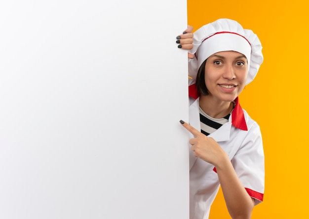 Glimlachende jonge vrouwelijke kok in eenvormige chef-kok die zich achter witte muur bevindt en op het richt geïsoleerd op oranje muur
