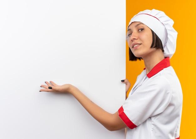 Glimlachende jonge vrouwelijke kok in eenvormige chef-kok die zich dichtbij witte muur bevindt en met hand wijst naar het geïsoleerd op oranje muur
