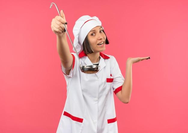 Glimlachende jonge vrouwelijke kok in eenvormige chef-kok die zich uit pollepel uitstrekt en lege die hand toont die op roze muur wordt geïsoleerd