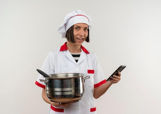 Glimlachende jonge vrouwelijke kok in pot en mobiele telefoon van de chef-kok de eenvormige die op witte muur wordt geïsoleerd