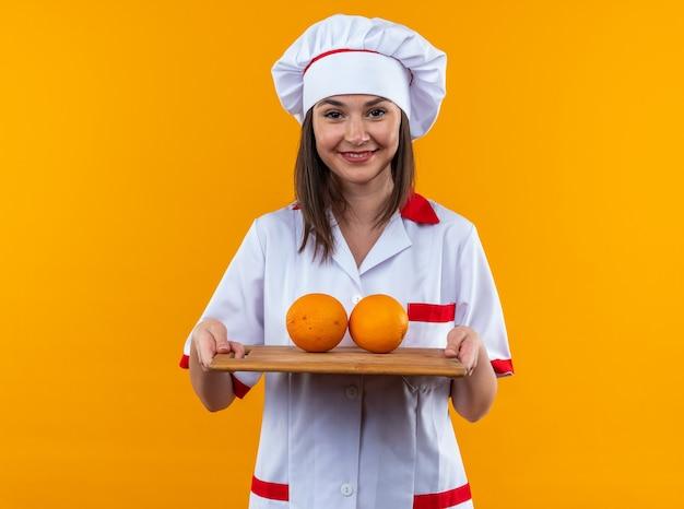 Glimlachende jonge vrouwelijke kok in uniform van de chef-kok met sinaasappels op snijplank geïsoleerd op oranje muur