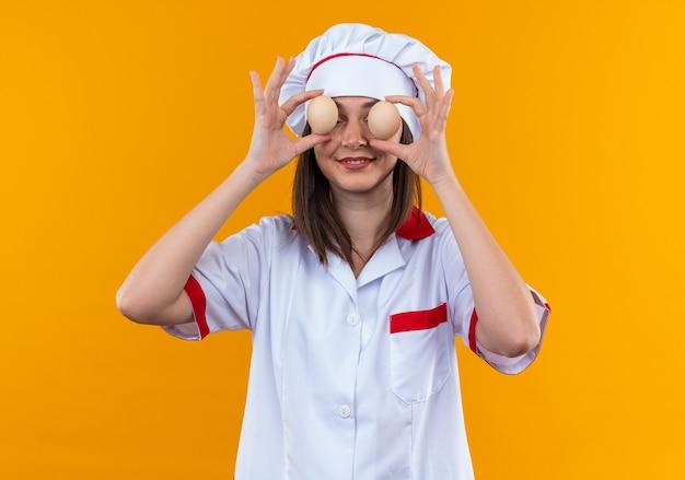 Glimlachende jonge vrouwelijke kok met chef-kok uniform bedekte ogen met eieren geïsoleerd op oranje muur