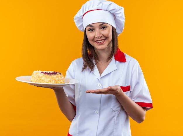 Glimlachende jonge vrouwelijke kok met chef-kok uniform bedrijf en wijst naar taart op plaat geïsoleerd op oranje achtergrond