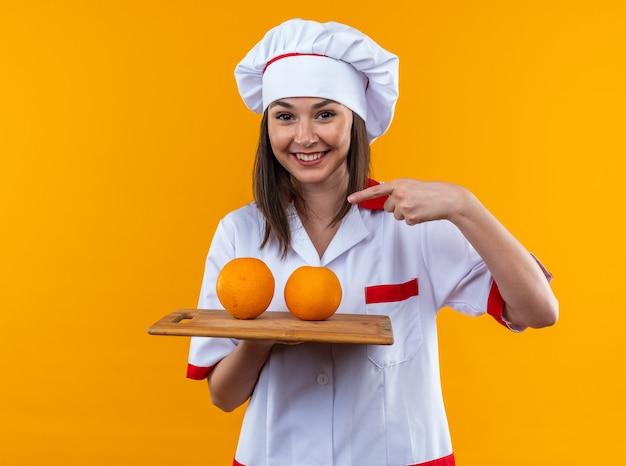 Glimlachende jonge vrouwelijke kok met een uniforme chef-kok die vasthoudt en wijst naar sinaasappels op een snijplank geïsoleerd op een oranje muur