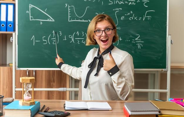Glimlachende jonge vrouwelijke leraar met een bril zit aan tafel met schoolbenodigdheden op het bord met een aanwijzer die duim omhoog laat zien in de klas