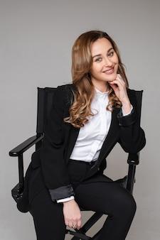 Glimlachende jonge vrouwelijke ondernemersonderneemster in zwart kostuumzitting op bureaustoel op grijze studiomuur.