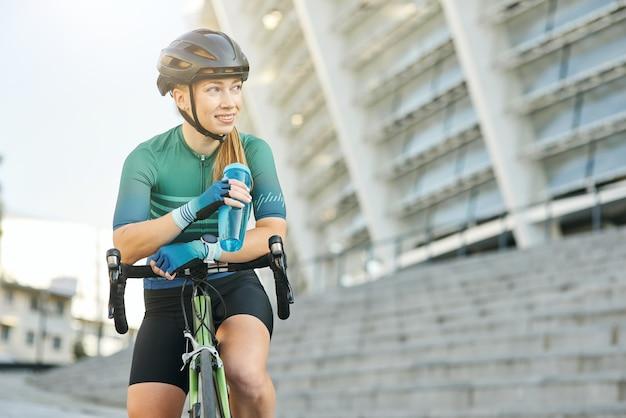 Glimlachende jonge vrouwelijke professionele wielrenner die wegkijkt terwijl hij een waterfles vasthoudt