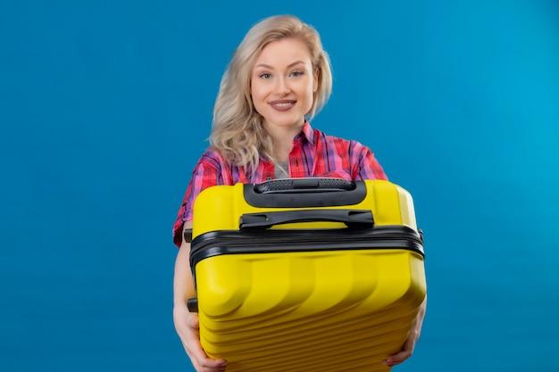 Glimlachende jonge vrouwelijke reiziger die de rode koffer van de overhemdsholding op geïsoleerde blauwe muur draagt