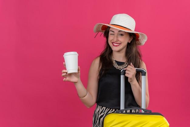 Glimlachende jonge vrouwelijke reiziger die zwart onderhemd draagt in hoed die knippert en kopje koffie op rode muur houdt