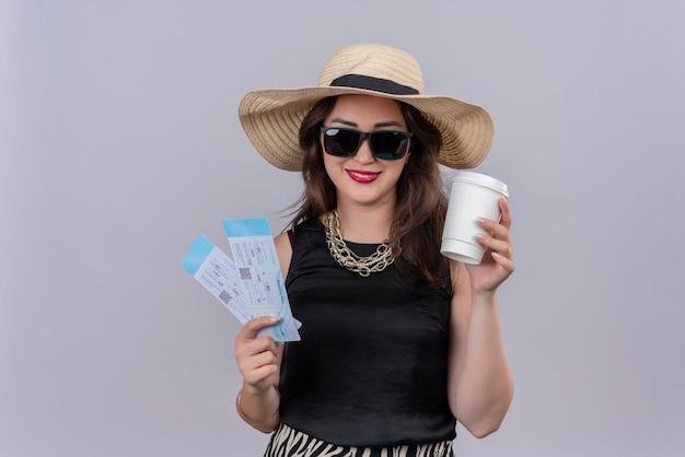 Glimlachende jonge vrouwelijke reiziger die zwart onderhemd in hoed draagt en in glazen kaartjes en een kop van koffie op witte muur houdt