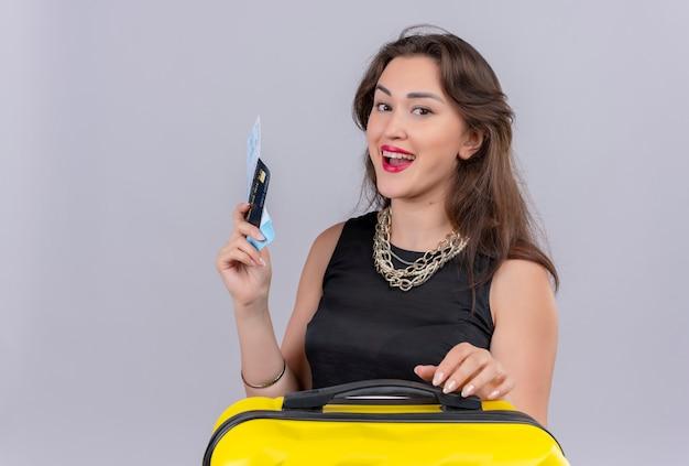 Glimlachende jonge vrouwelijke reiziger die zwarte onderhemdjes draagt ?? die kaartjes houdt en haar hand op koffer op witte muur legt