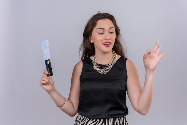 Glimlachende jonge vrouwelijke reiziger die zwarte onderhemdjes draagt die kaartjes houdt en okey gebaar op witte muur toont