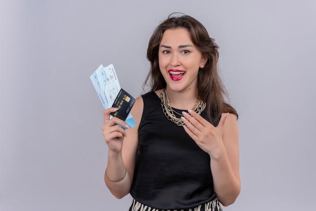 Glimlachende jonge vrouwelijke reiziger die zwarte onderhemdjes draagt die kaartjes houdt en wijst naar kaartjes op witte muur