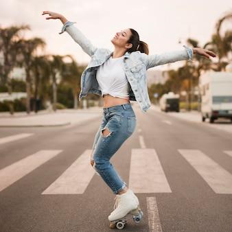 Glimlachende jonge vrouwelijke skater die op het zebrapad in evenwicht brengt