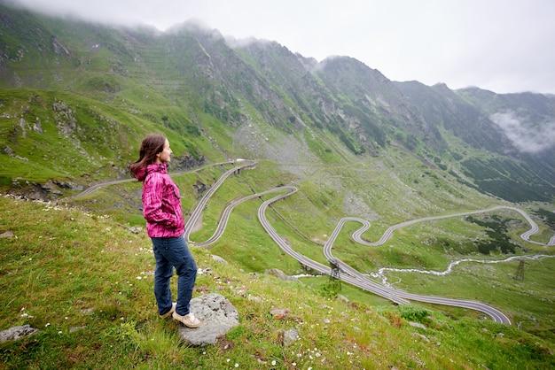 Glimlachende jonge vrouwelijke toerist die ver kijkt tijdens het reizen door een van de beste toeristische attracties die de bergweg van transfagarashan in roemenië slingeren