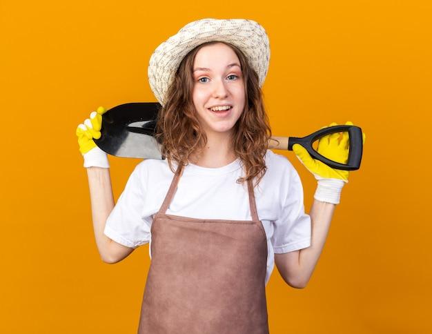 Glimlachende jonge vrouwelijke tuinman die tuinhoed en handschoenen draagt die spade op schouder houden die op oranje muur wordt geïsoleerd