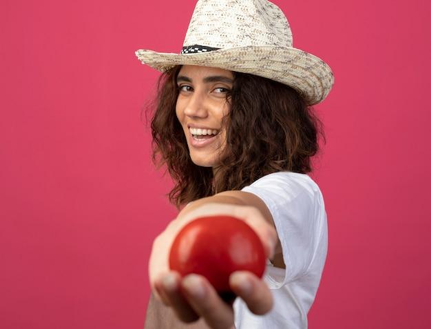 Glimlachende jonge vrouwelijke tuinman in eenvormig die het tuinieren hoed draagt die tomaat standhoudt