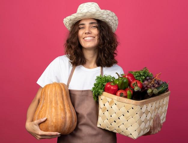 Glimlachende jonge vrouwelijke tuinman in uniform die tuinieren hoed draagt die plantaardige mand met pompoen houdt die op roze wordt geïsoleerd