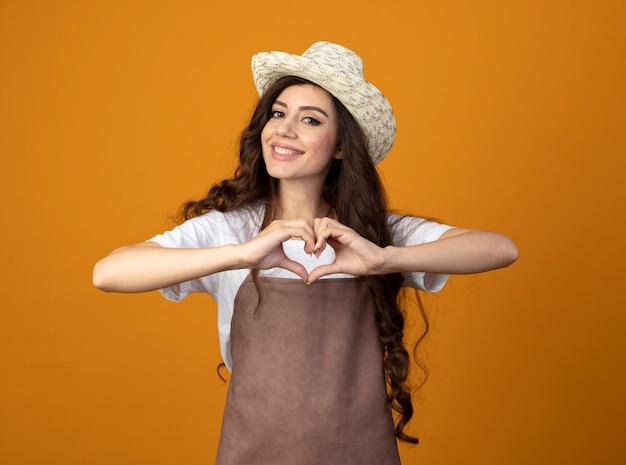 Glimlachende jonge vrouwelijke tuinman in uniform dragen tuinieren hoed gebaren hart hand teken geïsoleerd op oranje muur met kopie ruimte
