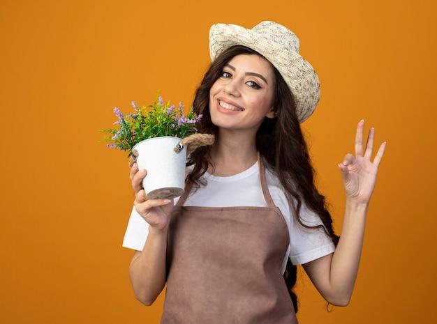 Glimlachende jonge vrouwelijke tuinman in uniform dragen tuinieren hoed houdt bloempot en gebaren ok handteken geïsoleerd op oranje muur met kopie ruimte