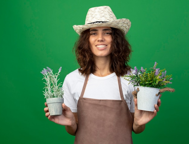 Glimlachende jonge vrouwelijke tuinman in uniform dragen tuinieren hoed met bloemen in bloempotten geïsoleerd op groene muur