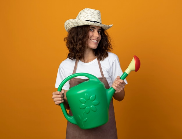 Glimlachende jonge vrouwelijke tuinman in uniform dragen tuinieren hoed met gieter