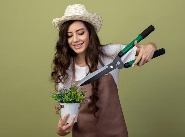 Glimlachende jonge vrouwelijke tuinman in uniform met tuinieren hoed houdt tuinknipper over bloemen in bloempot geïsoleerd op olijfgroene muur