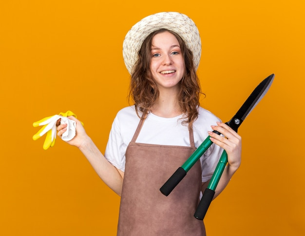 Glimlachende jonge vrouwelijke tuinman met een tuinhoed die een snoeischaar vasthoudt met handschoenen geïsoleerd op een oranje muur