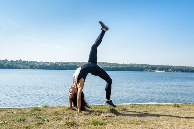 Glimlachende jonge vrouwelijke turnster springt in split buiten in de buurt van het meer. gezonde levensstijl.