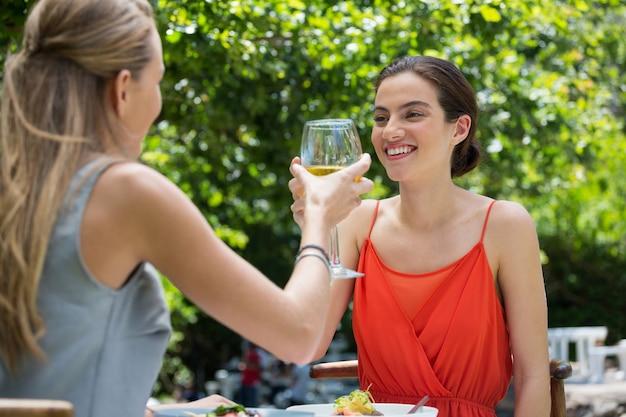 Glimlachende jonge vrouwelijke vrienden die wijnglazen roosteren bij restaurant