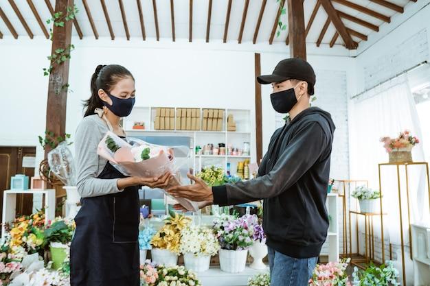 Glimlachende jonge vrouwelijke winkelier die een gezichtsmasker en een schort draagt. het onderhouden van mannelijke kopers van flanellen bloemen in de bloemenwinkel