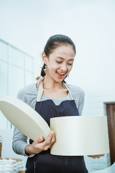 Glimlachende jonge vrouwelijke winkelier die een pakket ontvangt