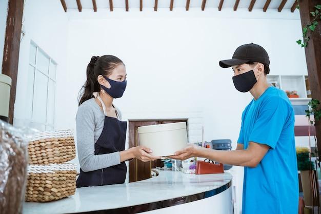 Glimlachende jonge vrouwelijke winkelier die een pakket van koerier ontvangt na gezond protocol
