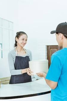 Glimlachende jonge vrouwelijke winkelier die een pakket van koerier ontvangt