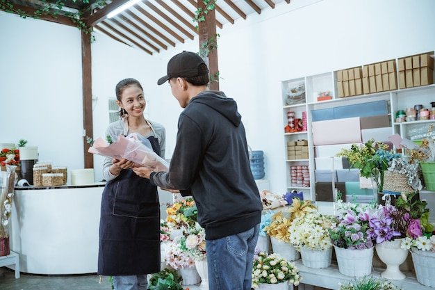 Glimlachende jonge vrouwelijke winkelier die een schort draagt. het onderhouden van mannelijke kopers van flanellen bloemen in de bloemenwinkel Premium Foto