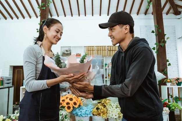 Glimlachende jonge vrouwelijke winkelier die een schort draagt. het onderhouden van mannelijke kopers van flanellen bloemen in de bloemenwinkel