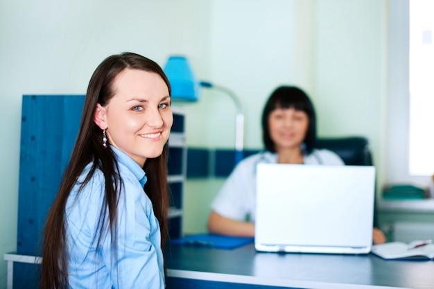Glimlachende jonge vrouwen bij artsenbureau