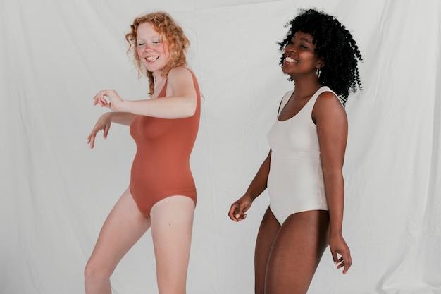 Glimlachende jonge vrouwen die tegen grijze achtergrond dansen