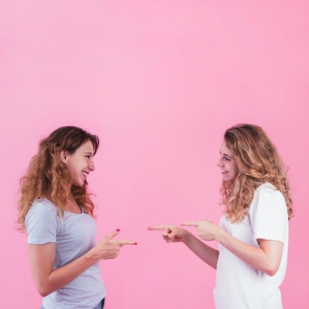 Glimlachende jonge vrouwen die vingers richten aan elkaar tegen roze achtergrond