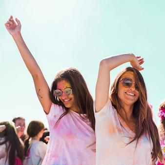 Glimlachende jonge vrouwen die zonnebril dragen die bij holifestival dansen