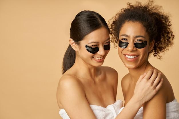 Glimlachende jonge vrouwen gewikkeld in een handdoek poseren met aangebrachte zwarte hydrogel onder ooglapjes