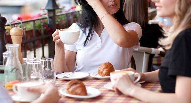 Glimlachende jonge vrouwen in café koffie drinken met croissant. communicatie en vriendschap concept.
