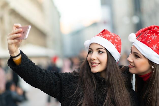 Glimlachende jonge vrouwen in kerstmishoed die een beeld samen nemen