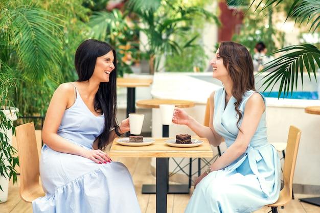 Glimlachende jonge vrouwen met koffiekoppen en vrede van cake bij koffie.