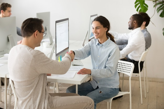 Glimlachende jonge vrouwenhandenschudden tevreden cliënt makend overeenkomst in bureau