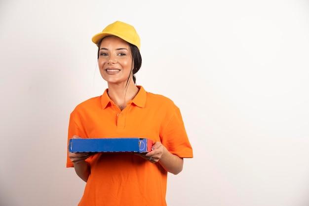 Glimlachende jonge vrouwenkoerier die eenvormig en glb draagt dat doos in handen houdt.