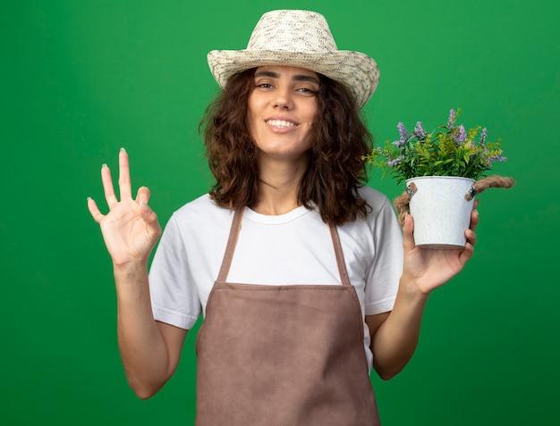Glimlachende jonge vrouwentuinman die in uniform tuinieren hoed dragen die bloem in bloempot houden en oke gebaar tonen dat op groen wordt geïsoleerd